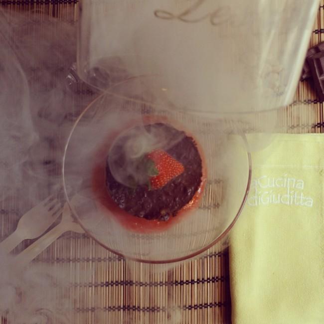 Tortino vegano di cioccolato fondente e mandorle su purea di fragole scottate al Calvados affumicato al legno di cedro